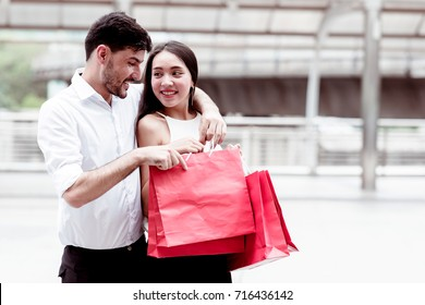Happy couple talking after a hard day of huge sale shopping in asian country. Young handsome white male and beautiful asian female with red shopping bag looking very satisfy. Apply urban looks.