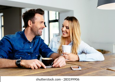 Happy couple talking at cafe looking at each other