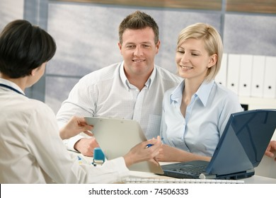 Happy couple talking to medical specialist, sitting at doctor's office smiling.?
