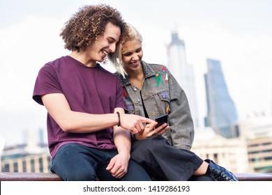 Happy couple talking sitting near River Thames, London. UK