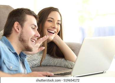 Happy couple talking and waving hand in a video conference on line with a laptop on a sofa at home