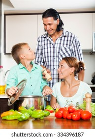 happy couple with teenager son cooking veggy lunch together in home kitchen