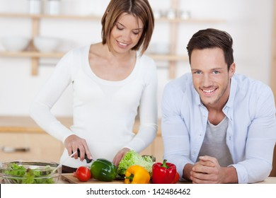 Happy couple in their Kitchen at home preparing vegetable salad