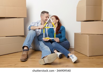 happy couple in their new house with cardboard boxes