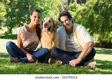 Happy couple with their pet dog in the park on a sunny day