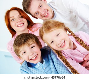 Happy couple and their two children smiling while looking at camera