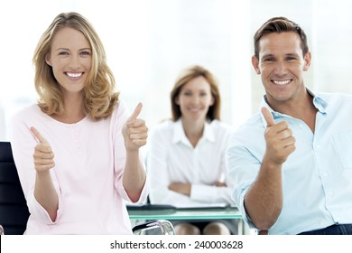 Happy couple with thumbs up at a meeting with female adviser.