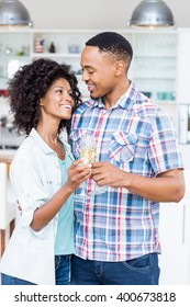 Happy couple toasting champagne glass in kitchen at home