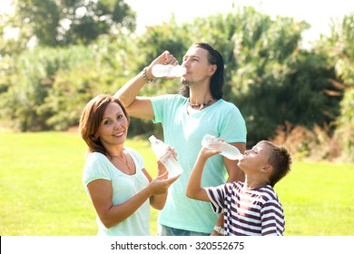 Happy couple together with children drinking water from plastic bottles in summer