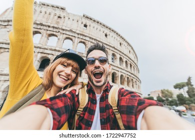 Happy couple of tourist having fun taking a selfie in front of Colosseum in Rome. People travel Rome, Italy.