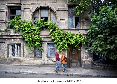 Happy couple of tourist near vintage house with round window at old streets of central Tbilisi, Georgia