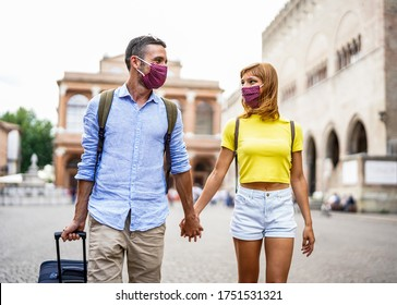 Happy couple of tourist wearing mask to protect from Covid-19 are walking in the city holding hands and suitcase. New normal travel concept.