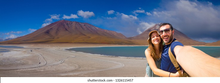 Happy couple tourists backpacker taking selfie in Laguna Verde, the salt lake at the foot of the volcanos Licancabur and Juriques. Eduardo Avaroa Andean Fauna National Reserve, Bolivia. South America
