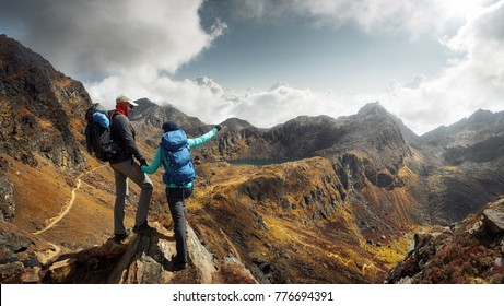 Happy couple tourists with backpacks in mountains enjoying panoramic on view of sunny mountains during a hike in the national park Lantang, Himalayas. Travel, happiness emotion, summer holiday concept