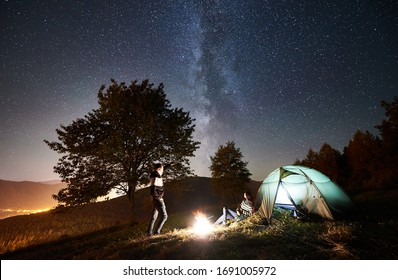 Happy couple tourists having a rest at bonfire near glowing tent. Man pointing at night sky full of stars and Milky way. On background beautiful starry sky, mountains, big tree and luminous city