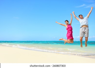 Happy couple tourists jumping on beach vacations. Travel concept of young couple cheering for summer holidays showing success, happiness, and joy on perfect white sand tropical beach under the sun.