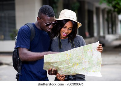 Happy couple of tourists, man and woman traveling on vacation and together look at the map