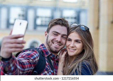 Happy couple of tourists taking selfie in showplace of city. Man and woman making photo on city background.