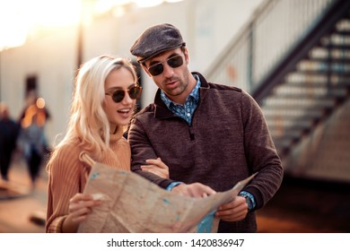 Happy couple of tourists using map in city.