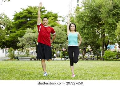 Happy couple training in the park - Young man and woman during summer workout and sport activity