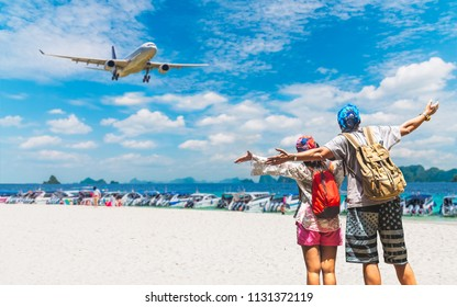 Happy couple travelers with backpack joy and fun on white sandy beach near airport at sunny day, Travel Phuket Thailand, Tourism destination place Asia, Tourist on summer holiday outdoor vacation trip