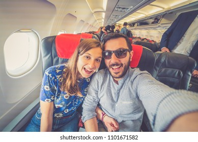 happy couple traveling around the world  and take selfie in the airplane