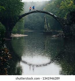 Happy couple traveling. Bridge in Kromlau, Saxony, Germany. Creative Artistic image.