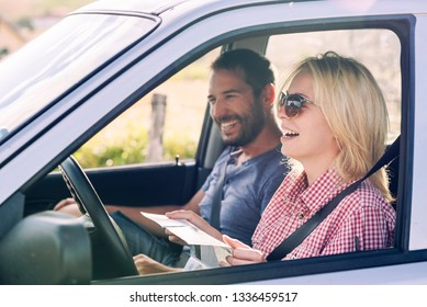 Happy couple traveling by car in nature and looking in map. Carefree friend travelers on countryside roadtrip journey. Young woman and man driving to adventure holiday.
