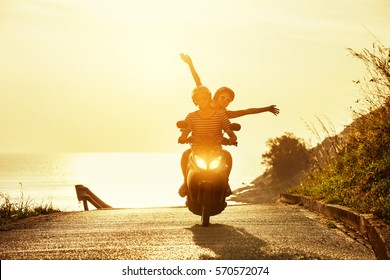 Happy couple traveling on motorcycle on sea coastal road. Travel concept