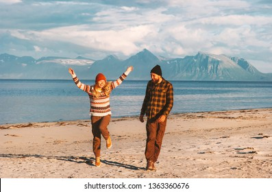 Happy couple traveling together joyful walk on beach in Norway man and woman lifestyle  summer vacations outdoor