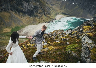 Happy couple traveling. Wedding couple travelers on a hill in Norway, Kvalvika. Beautiful view of the beach, Lofoten, Norway.