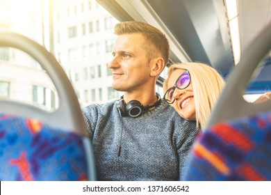 Happy couple travelling by bus in London - Beautiful blonde woman leaning on boyfriend shoulder and looking out of the window - Lifestyle and travel concepts in the city