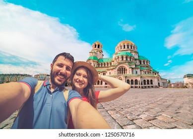 Happy couple travelling in Sofia, Bulgaria, taking photo selfie in front of the main cathedral