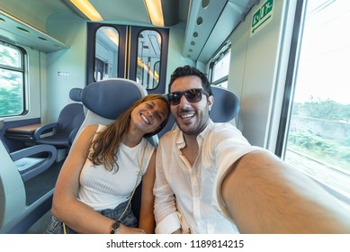 happy couple travelling take selfie on the train