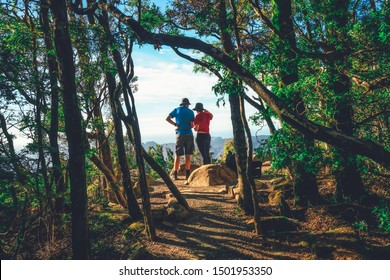 Happy couple trekkers hiking in forest and standing at cliff of Three Capes Track near Port Arthur in Tasmania, Australia. Summer journey activity and leisure backpack traveling.