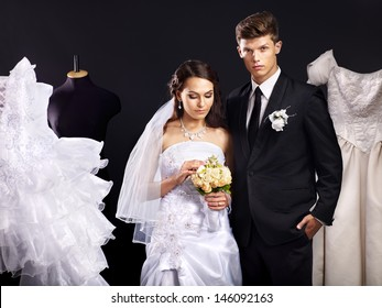 Happy couple try wedding dress in shop.