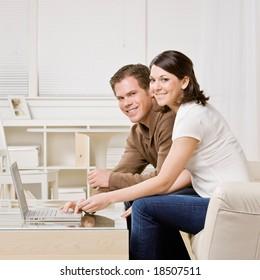 Happy couple typing on laptop in livingroom