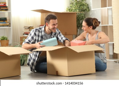 Happy couple unboxing belongings moving house sitting on the floor