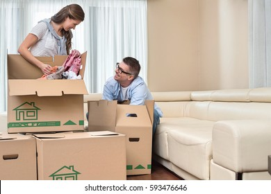 Happy couple unpacking cardboard boxes in new home