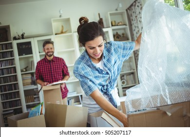 Happy couple unpacking cartons in their new house
