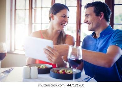 Happy couple using a digital tablet during lunch in restaurant