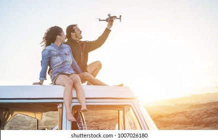 Happy couple using a drone sitting on top of vintage minivan at sunset - Young people having fun with new technology trends during holidays - Travel, tech and vacation concept - Focus on bodies
