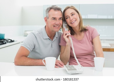 Happy couple using landline phone together in the kitchen at home