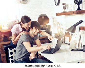Happy couple using laptop at home, smiling, pointing to screen.