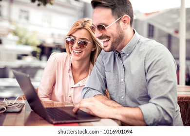 Happy couple using laptop,spending time together at coffee shop.Casual meeting ,outside office concept.Funny and happy moment.