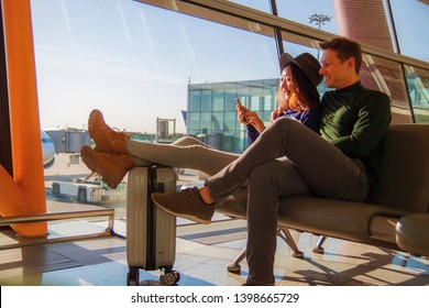 Happy couple using mobile phone at airport.