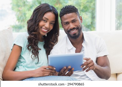 Happy couple using tablet together on the couch at home in the living room