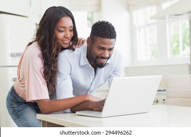 Happy couple using their laptop at home in the kitchen