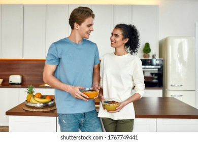 Happy couple, vegetarians looking at each other while standing in the kitchen. Young man and woman holding smoothie bowls. Vegetarianism, healthy food, diet, stay home concept. Front view