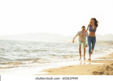 happy couple waling on the beach and having fun